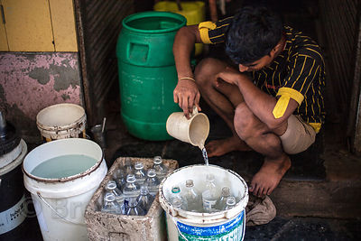 A man fills up bottles of water with unfiltered tap water to sell, in Dharavi, by most account the most crowded square mile on Earth, with about a million people. Water is rationed by the government of Mumbai and is subject to random restrictions and the performance of monsoon rains.