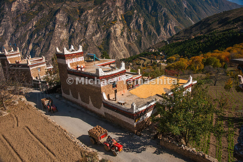 "A loaded tractor rolls past a fortress-like home in Danba, known as ""The Kingdom of Watchtowers"" and ""Beauty Valley."""