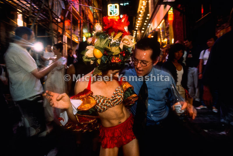 Revelers twist and shout at the Madhatters Party, an AIDS fundraising event let loose in the neighborhood of Lan Kwai Fong, hangout of the young expatriate set. For many old-timers, however, China has crashed Hong Kong's party, triggering a large-scale exodus.