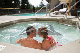August 24, 2015: Whistler BC. A couple enjoys the hot tub at Whistlers Crystal Lounge on a sunny summer day. Photo by Brad Kasselman - coastphoto.com