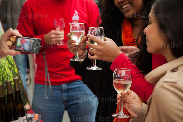 Young mixed race friends toast and drink wine