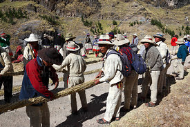 Men twisting the thin grass ropes together to make the thicker ropes for rebuilding the bridge, Q'eswachaka , Canas province , Peru