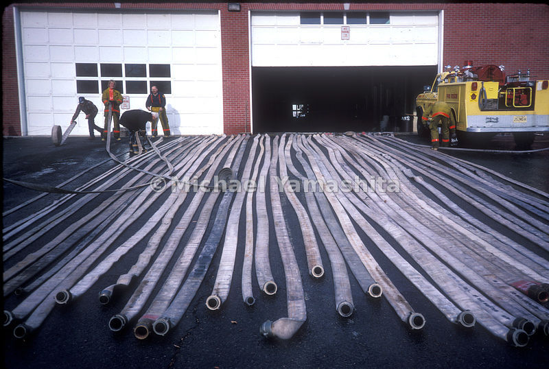Fire hose laying out in front of firehouse to dry.