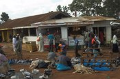 Street market stalls outside butchers with people shopping, Kampala shanty town Uganda Africa