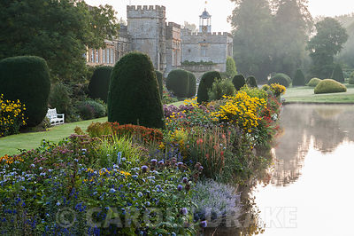 The Long Pond with house beyond, edged by the herbaceous border planted with heleniums, kniphofias, dahlias, asters and eupatoriums. Forde Abbey, nr Chard, Dorset, UK