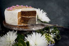 Marzipan Almond Cake with a Orange Blossom Mascarpone Frosting on a wooden pedestal, served with Rosé wine.  Photographed on a black/gray background.