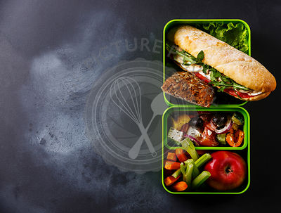 Take out food Lunch box with Tuna and egg Sandwich, Greek salad and vegetables on blackboard background copy space