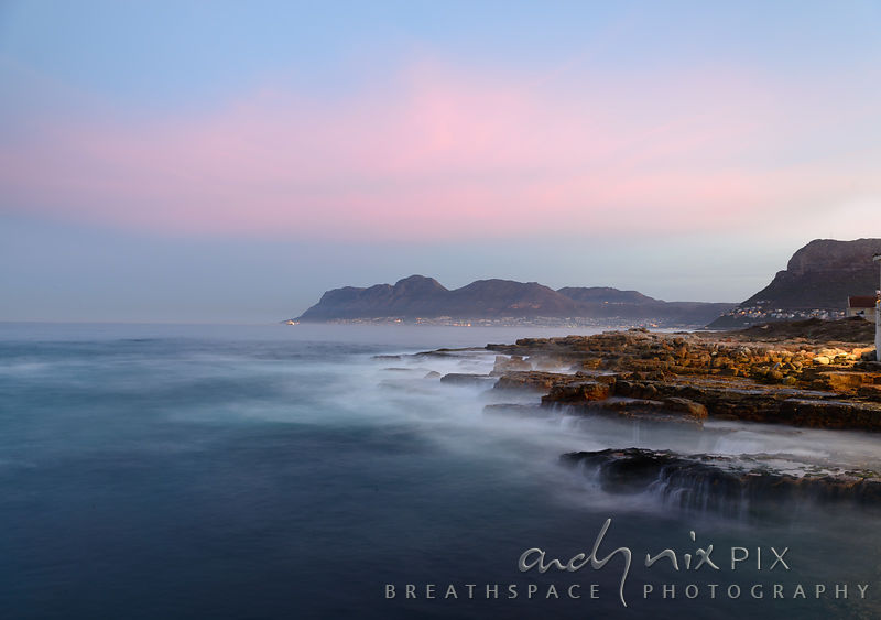 View of waves breaking over rocks in foreground, Simpns Town in distance at sunset