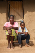 Mother and son sitting on a low stool outside their rural home in Kenya.