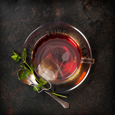 Cup of tea and mint on rustic background