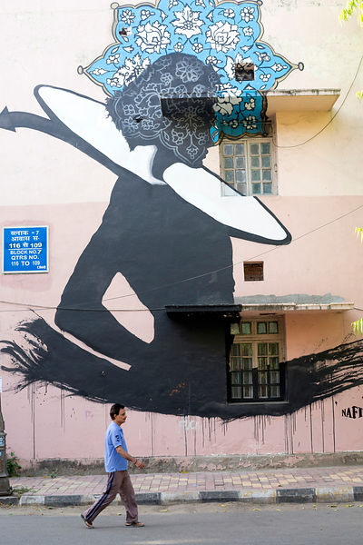 A man walks past street art in the Lodhi Colony area of New Delhi