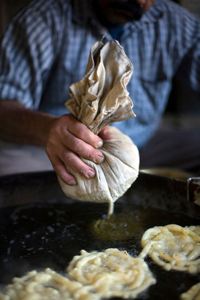India - Delhi - A man squeezes batter from a cloth to make jalebis