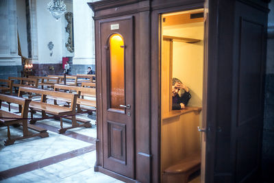 A priest awaits confessions in Catania Cathedral, Catania.