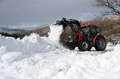 Clearing rural road with tractor and loader after snow storm has blocked it. Cumbria, UK.