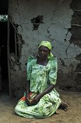 African woman wearing green dress kneeling on floor outside hut, Mbale Uganda Africa
