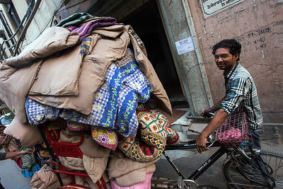 A man picks up laundry by cycle rickshaw, Delhi, India