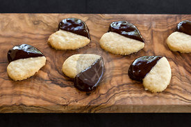 homemade chocolate dipped heart biscuits or cookies on olive wood board