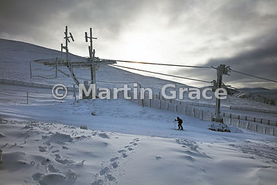 A solitary skier completes the trudge up Cairn Gorm Mountain with not-yet-working ski tow behind, November 22
