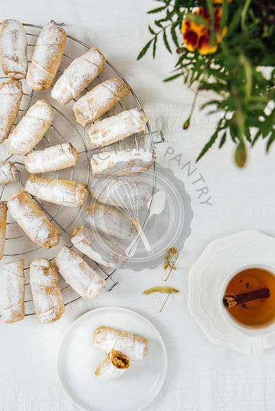 Turkish cookies stuffed with apple and cinnamon on a cooling rack on a white background photographed from top view. A cup of tea, a small plate with cookies and flowers accompany.