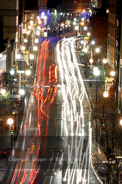 Traffic on a busy street, showing traffic trails from the car lights at night.  Location is Broad Street in Birmingham, England UK.