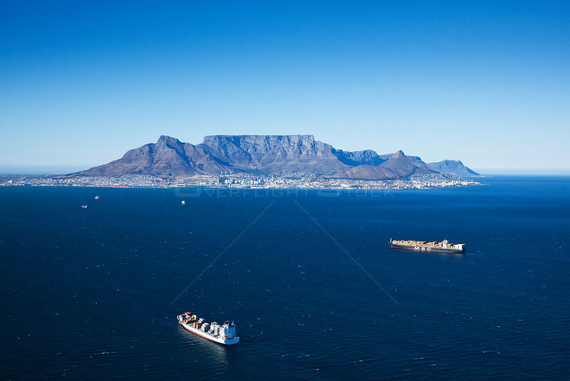 Aerial photograph of container ship with Cape Town in the distance, Atlantic Ocean, South Africa, Western Cape Province, March 2010