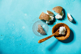 Organic healthy Coconut butter and fresh coconut pieces on bue background copy space