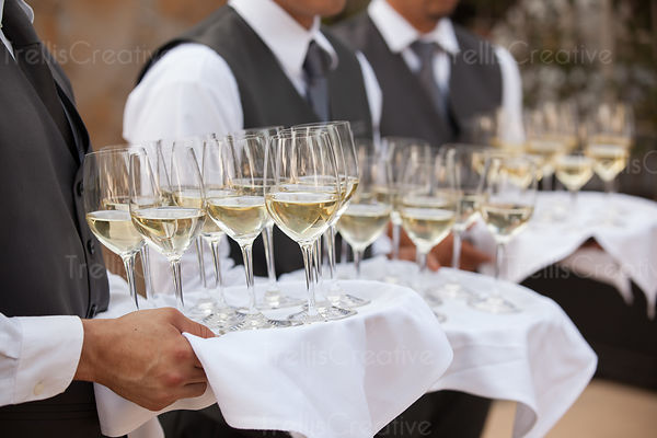 Waiters hold trays of wine for party guests