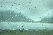 Rain drops on car window and fjord landscape