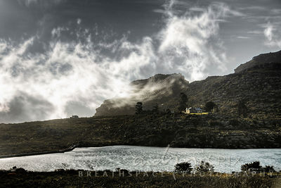 Clouds swirl above a lakeside house