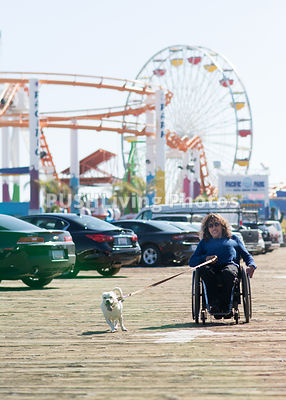 Man using a wheelchair on the Santa Monica Pier with his dog