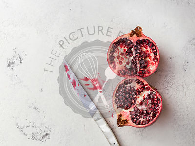 Cut pomegranate on a white textured surface with knife and spilled pomegranate juice.