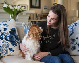 Young Woman Holding Her Cavalier King Charles Spaniel on Couch