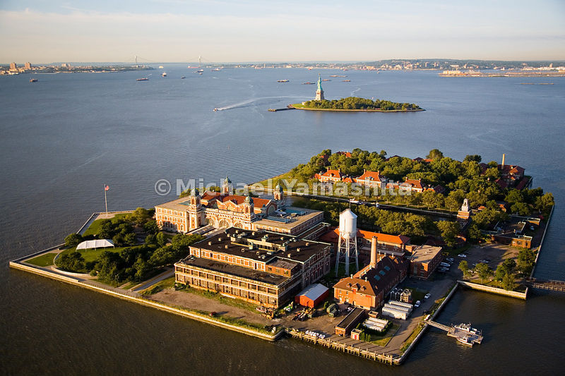 An aerial view of Ellis Island, where between 1890 and 1954, 12 million immigrants were processed after arriving on ships.  Today's Ellis Island is now a 27-acre National Park and Museum.  The Statue of Liberty can be seen in the background.
