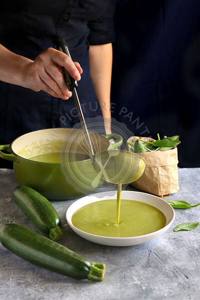 Female hand pouring spinach zucchini soup in a bowl