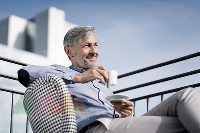 Smiling grey-haired man sitting on balcony and drinking coffee
