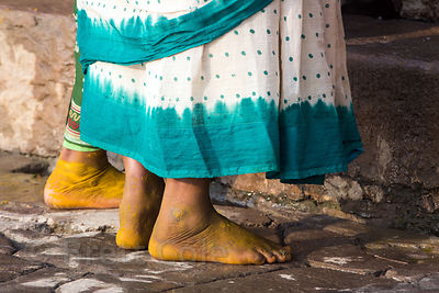 Women bathe in the Ganges River. Their feet are yellow because they've been covered in Turmeric to prevent infection from the heavily polluted water in the Ganges, Tulsi Ghat, Varanasi, India.