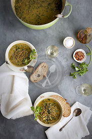 Green Lentil Coconut Soup in ceramic bowls served with bread and white wine.  Photographed on a gray background.