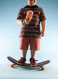 Young boy eating ice cream on sagging skate board
