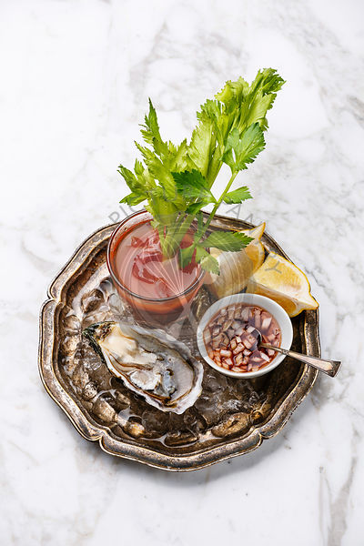 Open Oyster Fines de Claire and Bloody Mary cocktail on white marble background