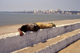 Boy asleep on wall overlooking Chowpatty Beach