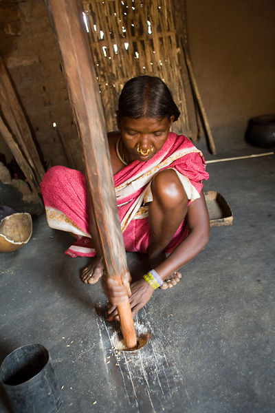 A tribal woman grinds and sifts grain