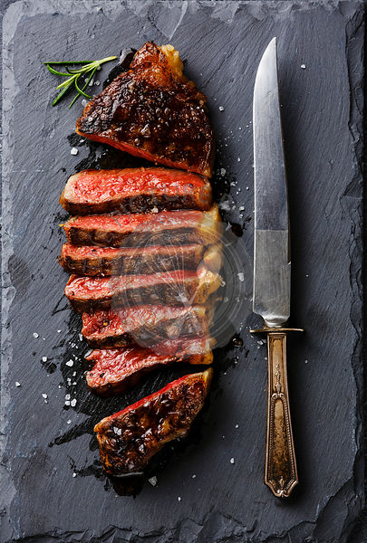 Sliced medium rare grilled Striploin steak and knife on slate board