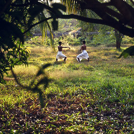 A dusk, two students practise dance moves in the grounds of the Kerala Kalamandalam