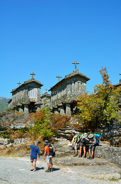 Walkers near the Espigueiros, the old and traditional stone granaries of Soajo. Peneda Geres National Park, Portugal