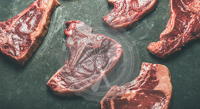 Fresh raw beef meat steak cuts over black stone background