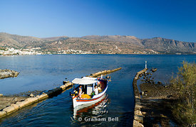 fishing boat entering elounda bay from the canal, elounda, crete, greece.
