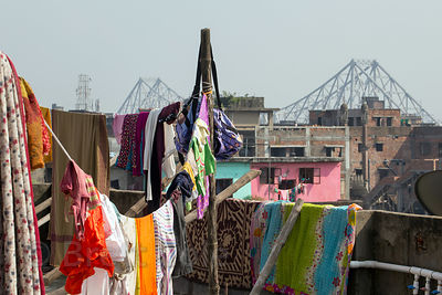 Rooftop view of laundry being dried with iconic Howrah Bridge in the distance, Howrah, India