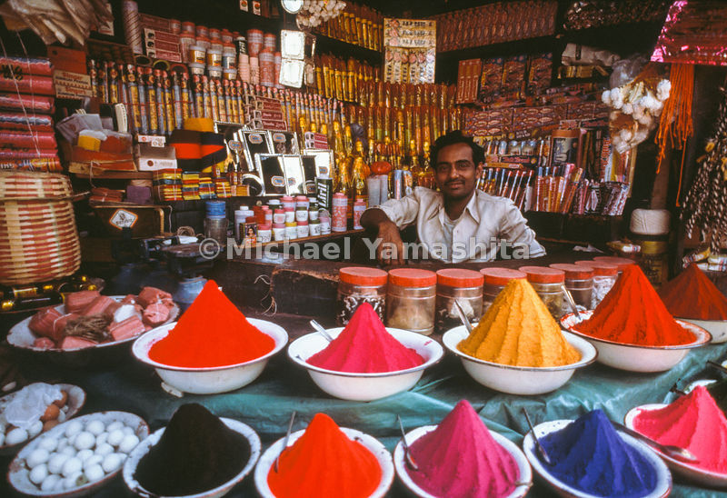 A merchant sells colored sand and other goods in his shop.