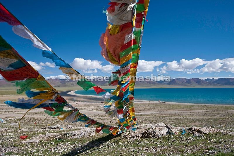 Prayer flags inscribed with Buddhist sutra (prayers) frame Namtso Lake in primary colors, representing the five basic elements.
