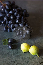 bunch of black grapes on green marble with two green figs in the foreground, still life